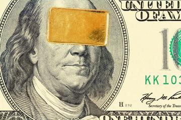 Gold bar on 100 dollar bill banknote closeup