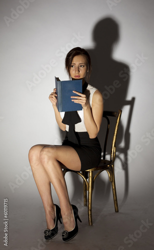 Girl sitting on a chair and reading a terrible book