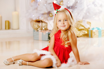 Beautiful little Santa girl near the Christmas tree.  Happy girl