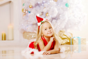 Beauty little Santa girl near the Christmas tree.  Happy girl wi