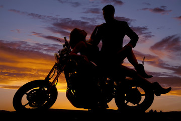 woman lay back on motorcycle man stand silhouette