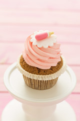 Cupcake with strawberry icing and pink background