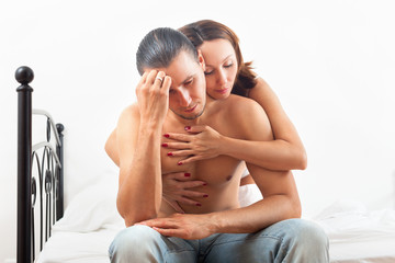 Woman consoling the depressed man in bedroom at home