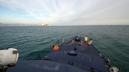 Coastguard ship sailing close to a container ship