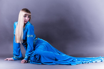 beautiful woman lying on the floor in a blue dress