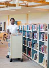 Librarian With Trolley Of Books In Bookstore