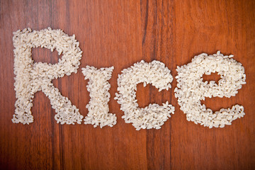 word of rice grains on a wooden background