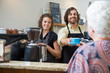 Cafe Owners Serving Coffee To Woman At Counter