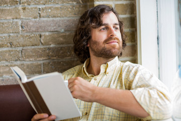 Man With Book Looking Through Window In Coffeeshop