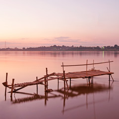 Tranquil sunset with a jetty on Mekong river in autumn.
