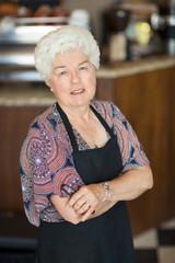Confident Senior Owner Standing In Coffeeshop