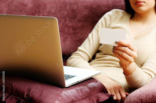 Young woman doing online shopping with blank credit card
