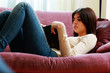 Young beautiful woman lying on the sofa and reading book at home