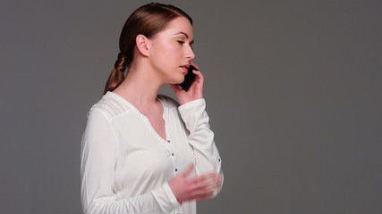 Caucasian Woman Talking Cell Phone While Isolated on Gray