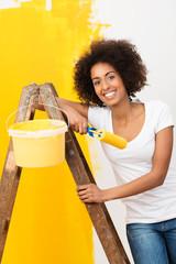 lachende frau streicht ihre wohnung gelb