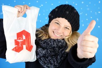 Frau im Winter mit Tüte aus Apotheke