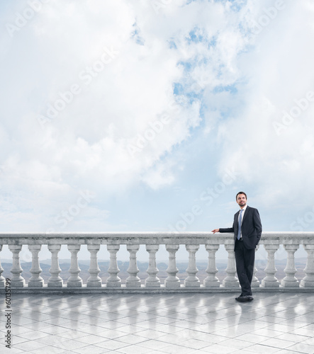 man standing on terrace overlooking the mountains