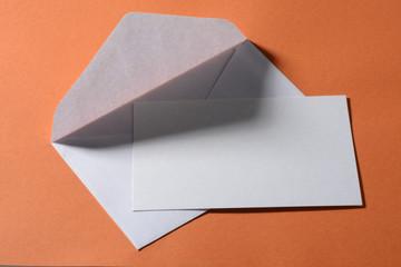 Sobre y tarjeta en blanco con fondo naranja
