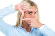 frau schaut durch fingerrahmen