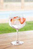Strawberry gin and tonic cocktail by a pool outdoors