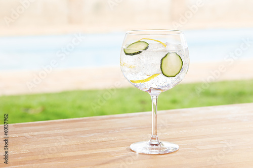Cucumber gin and tonic cocktail by a pool outdoors