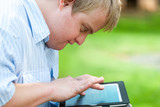 Kid with down syndrome playing on tablet. - Fine Art prints