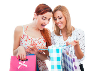 Surprised friends woman holding shopping bags