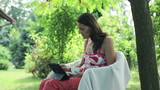 woman using her tablet and drinking coffee in the garden