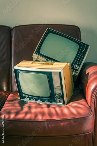 Two vintage televisions on red couch