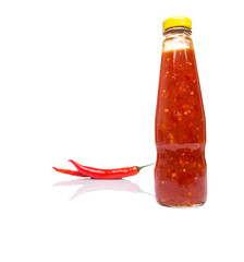 Fresh red chili and bottled chili sauce over white background