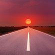 Leinwandbild Motiv Driving on an empty highway towards the setting sun