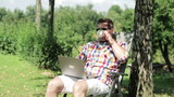 man working on his tablet and drinking coffee in the garden