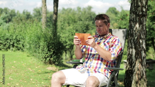 man playing on tablet in the garden