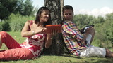 young couple sitting under the tree and using tablets