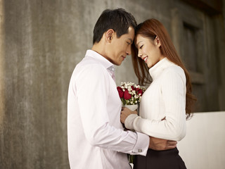 happy asian young lovers with flowers
