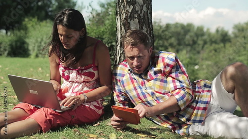 couple working on tablet and laptop under the tree shadow