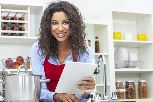 Woman Using Tablet Computer Cooking in Kitchen
