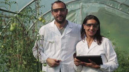 scientists smiling to the camera and standing in the greenhouse