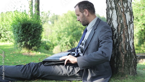 businessman finishing work and sitting under the tree