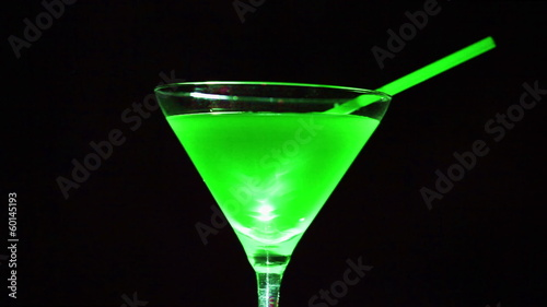 Green  cocktail. Wine  glass in rotation