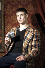 Portrait of young man with old film photocamera