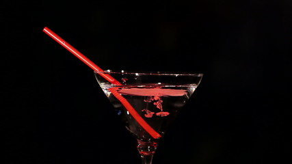 Blood drips in  cocktail wine glass with a straw
