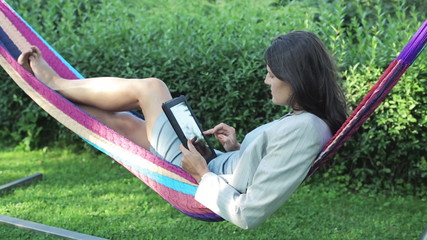 businesswoman working on tablet and swinging in a hammock