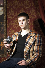 Portrait of young man with old film photocamera in hand