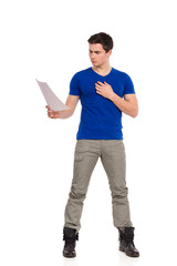Handsome young man reading document.