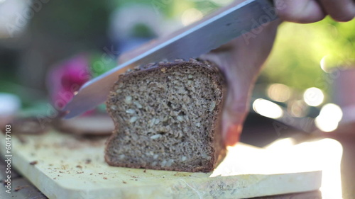 woman's hands slicing bread with a knife