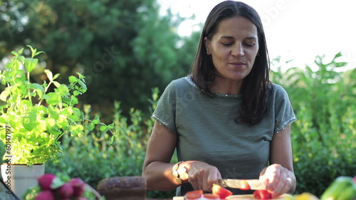 woman cutting tomato by the table in the garden