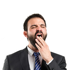 Businessman yawning over white background