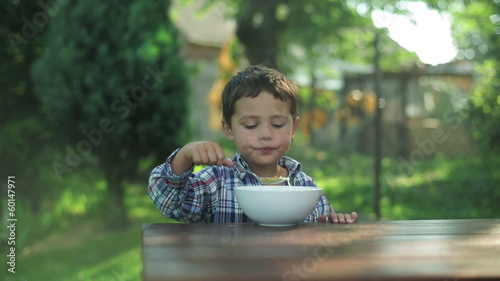 little boy eating soup by the table in the garden