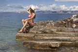 Beautiful girl with perfect tan sitting on the rock at sea